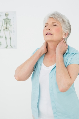 Senior woman suffering from neck pain with eyes closed in the medical office photo