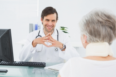 Portrait of a smiling male doctor listening to senior patient with concentration at the medical office photo
