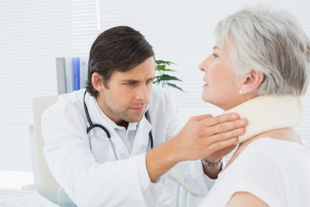 Male doctor examining a senior patients neck in the medical office photo