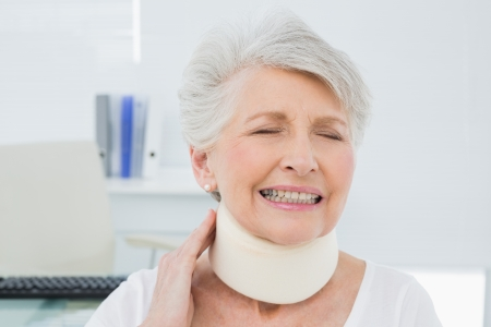 Close-up of a senior woman wearing cervical collar with eyes closed in the medical office photo