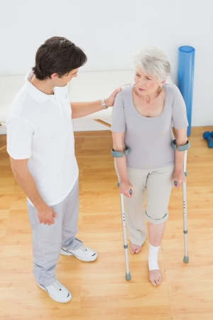Male therapist in discussion with a disabled senior patient in the gym at hospital Imagens