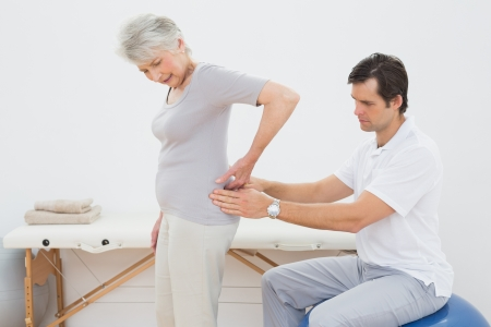 Side view of a male physiotherapist examining senior woman's back in the medical office