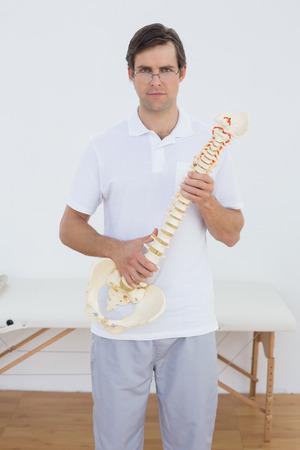 Portret van een zelfvertrouwen mannelijk arts bedrijf skelet model in zijn kantoor