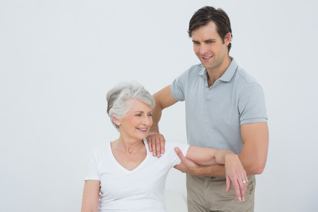 Male physiotherapist massaging a smiling senior woman's arm in the medical office