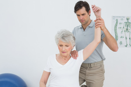 old man on a physical pressure: Male physiotherapist stretching a senior womans arm in the medical office