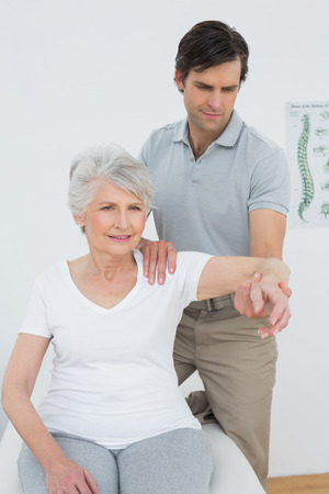 physical pressure: Male physiotherapist stretching a senior womans arm in the medical office