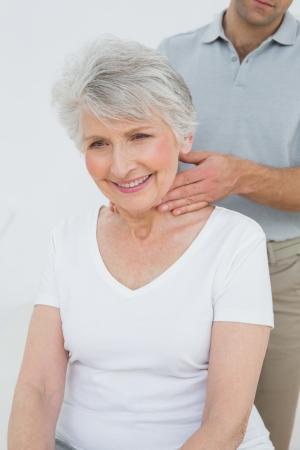 spinal manipulation: Maschio fisioterapista che massaggia il collo di una donna senior presso l'ufficio medico