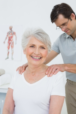 Male physiotherapist massaging a senior womans shoulders in the medical office photo