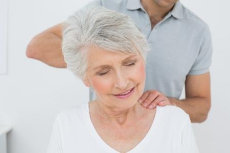 의료 사무실에서 수석 여자의 목을 마사지 남자 물리 치료사 스톡 콘텐츠