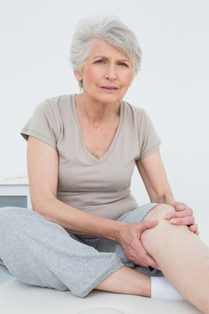 casuals: Portrait of a senior woman with a painful knee sitting on examination table Stock Photo