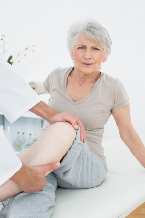 Portrait of a senior woman getting her leg examined at the medical office photo