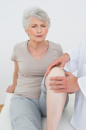 Displeased senior woman getting her knee examined at the medical office photo