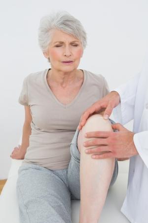 Misnoegd senior vrouw krijgt haar knie op de medische kantoor onderzocht