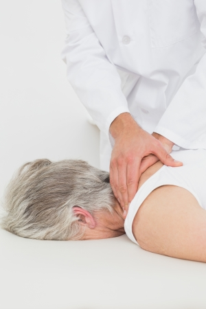 spinal manipulation: Close-up di un fisioterapista che massaggia la schiena di una donna senior presso l'ufficio medico Archivio Fotografico