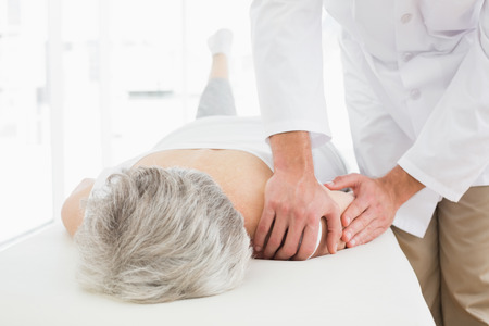 Close-up of a physiotherapist massaging a senior womans shoulder in the medical office photo