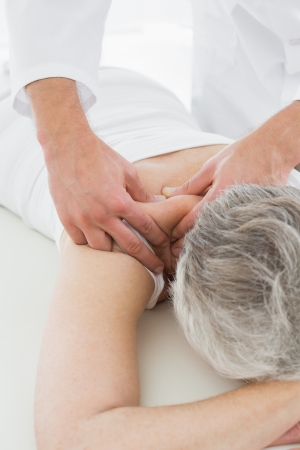 Close-up of a physiotherapist massaging a senior womans back in the medical office Stock Photo