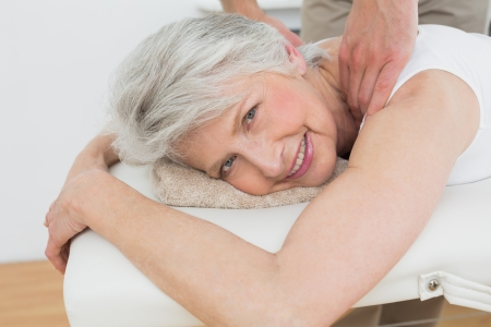 Male physiotherapist massaging a senior womans shoulder in the medical office