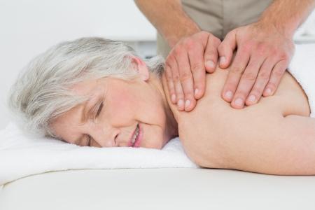 spinal manipulation: Close-up di un fisioterapista che massaggia la schiena di una donna senior in ufficio medico Archivio Fotografico