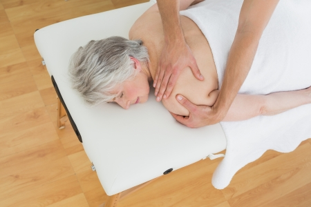 back sprains: High angle view of a physiotherapist massaging a senior womans back in the medical office