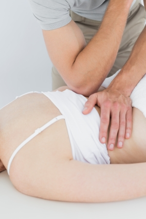 back sprains: Close-up of a male physiotherapist massaging a womans back in the medical office Stock Photo