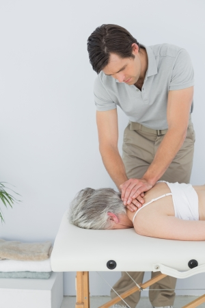 spinal manipulation: Maschio fisioterapista che massaggia la schiena di una donna senior in ufficio medico Archivio Fotografico