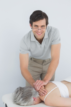 Portrait of a smiling male physiotherapist massaging a senior womans back in the medical office photo