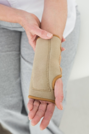 Close-up mid section of a woman with hand in wrist brace at the medical office photo