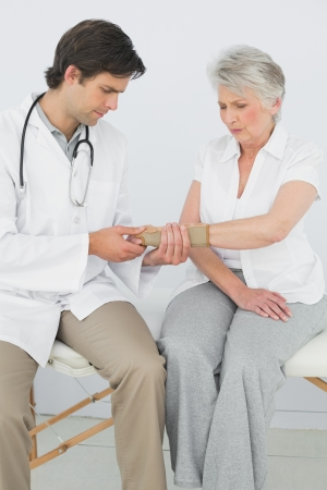 Male physiotherapist examining a senior womans wrist in the medical office photo