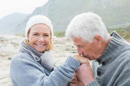 Side view of a senior man kissing happy woman\'s hand at the rocky beach
