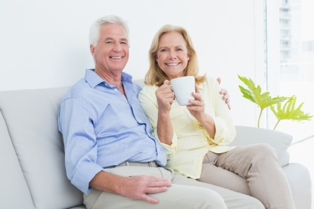 Relaxed senior couple with coffee cup sitting on sofa in a bright house photo