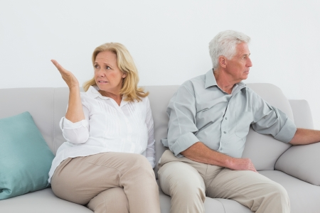 Displeased relaxed senior couple sitting on sofa in a house