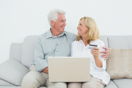 Relaxed senior couple doing online shopping through laptop and credit card on sofa in a house photo