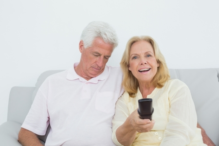 Relaxed senior couple watching television in a house photo