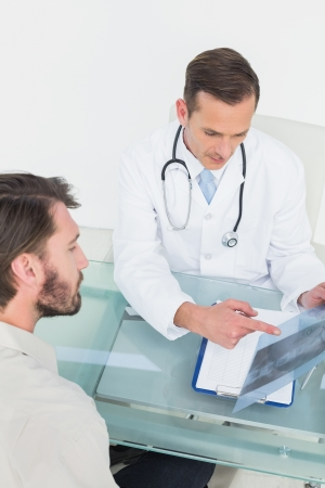 Male doctor explaining spine x-ray to patient in the medical office photo