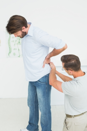 Side view of a male physiotherapist examining man's back in the medical office photo