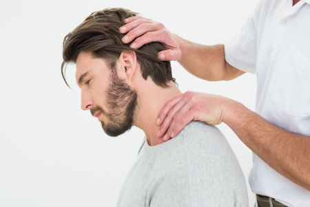 Side view of a young man getting the neck adjustment done in the medical office