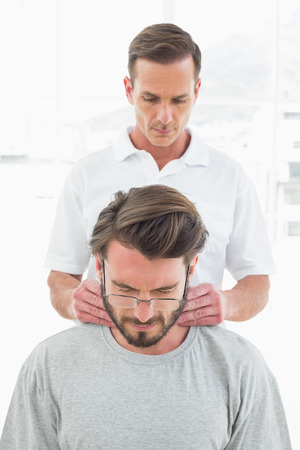 Male therapist massaging a young man's neck in the medical office photo