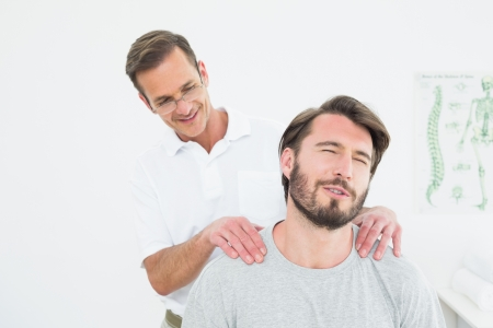 Male therapist massaging a content mans shoulders in the medical office