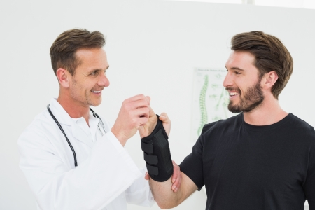 Male physiotherapist examining a young mans wrist in the medical office photo