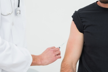 Close-up of hands injecting a young male patients arm over white background photo