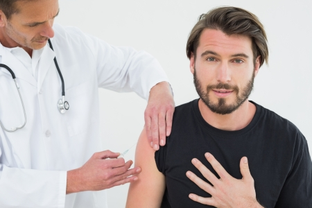 Male doctor injecting a young male patients arm over white background photo