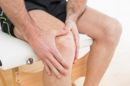 Close-up mid section of a young man with his hands on a painful knee while sitting on examination table photo