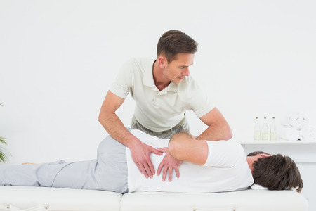 Male physiotherapist examining mans back in the medical office photo
