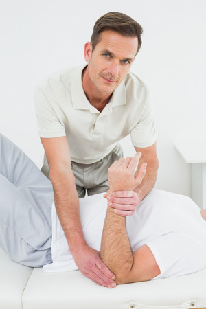 Portrait of a male physiotherapist examining a young mans hand in the medical office photo