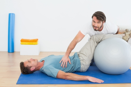 Physical therapist assisting young man with yoga ball in the gym at hospital photo