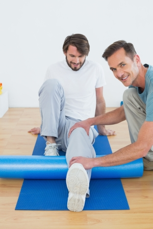 Physical therapist examining young mans leg at the hospital gym photo