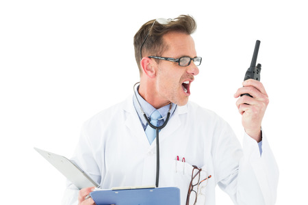 Annoyed doctor with clipboard shouting into a wireless radio over white background photo