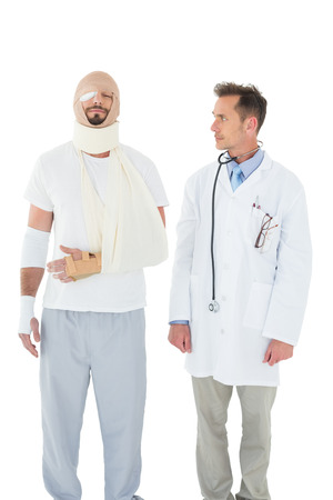 Doctor looking at a patient tied up in bandage over  white background photo