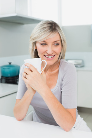 Thoughtful smiling casual young woman with coffee cup in the kitchen at home photo