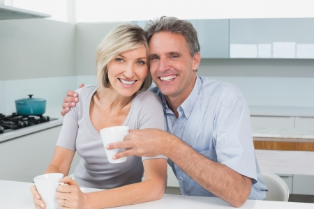 Portrait of a happy loving couple with coffee cups in the kitchen at home photo